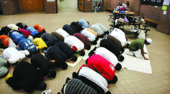 Muslim students kneeling in prayer